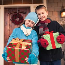 kids holding presents out their home