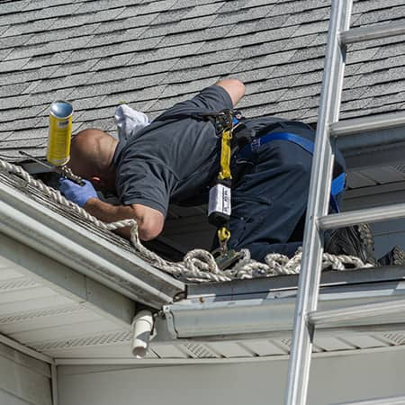 wildlife control technician patching holes in a ri roof