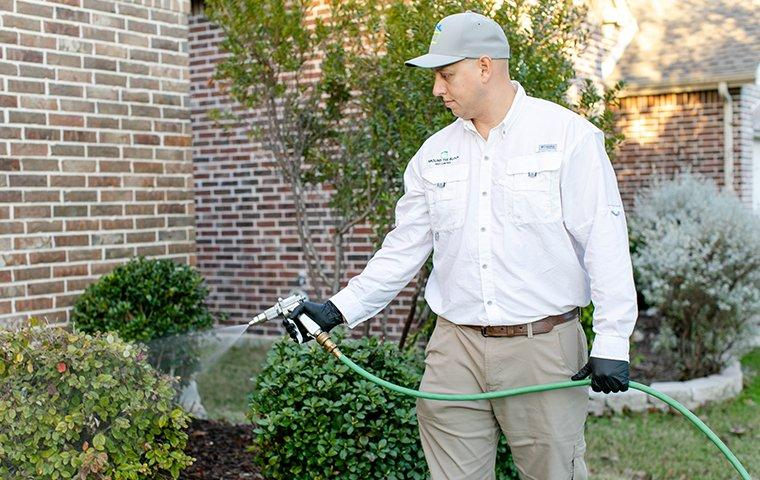 a tech spraying outside of a home