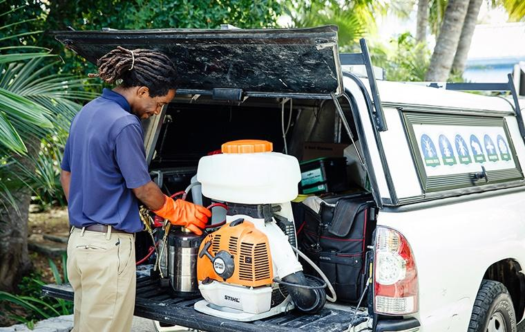 technician gathering mosquito control gear at home on grand turk island