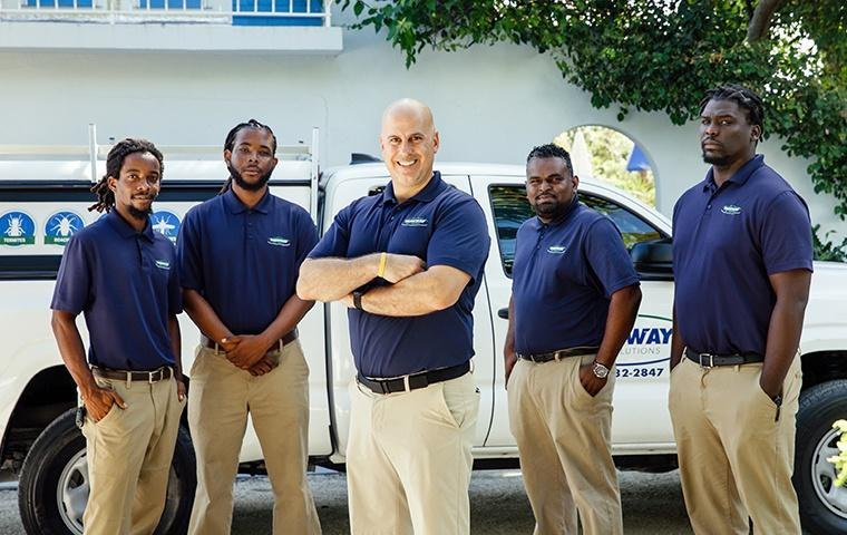 the turks and caicos pest experts standing beside a service vehicle