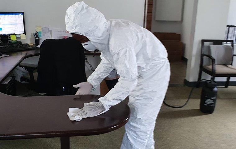 a tech wiping off a desk with a disinfecting wipe