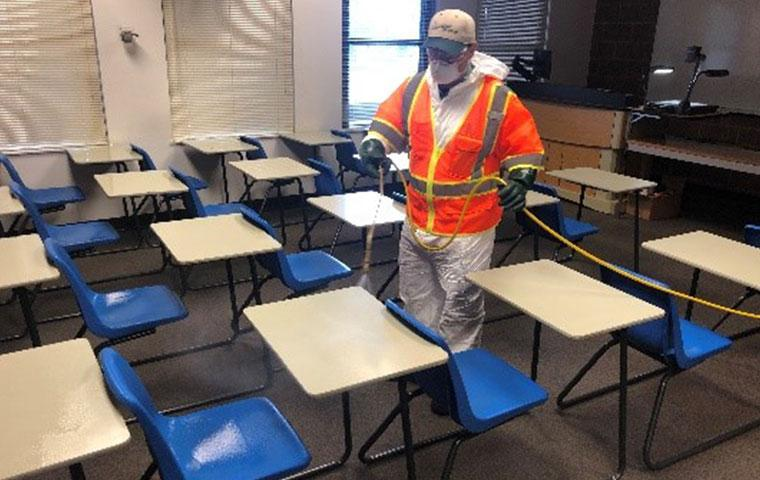 tech disinfecting an empty classroom