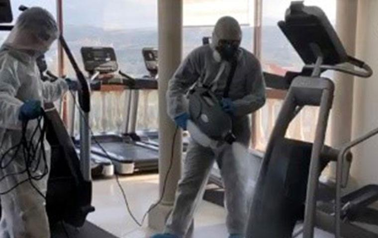 two techs disinfecting gym equipment