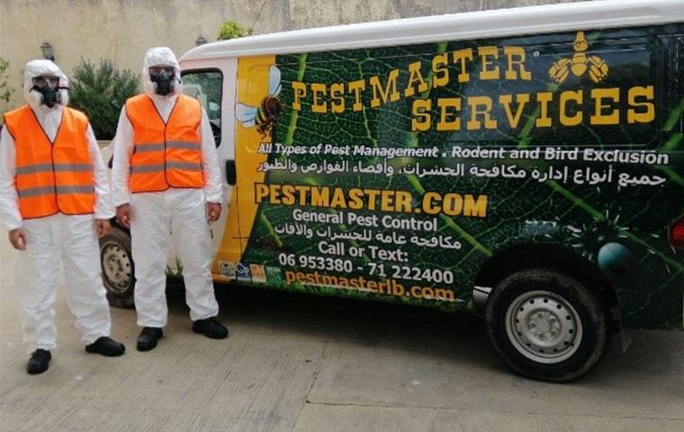 two pestmaster techs standing in front of company vehicle
