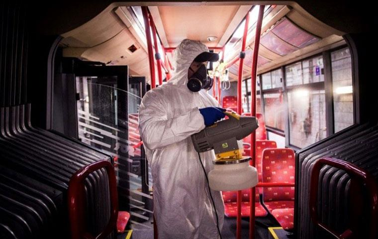 tech disinfecting a public transportation vehicle