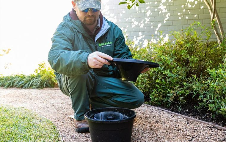 a technician kneeling over a mosquito trap in tarrant county