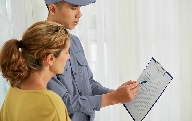 technician reviewing a clipboard with a homeowner in tarrant county
