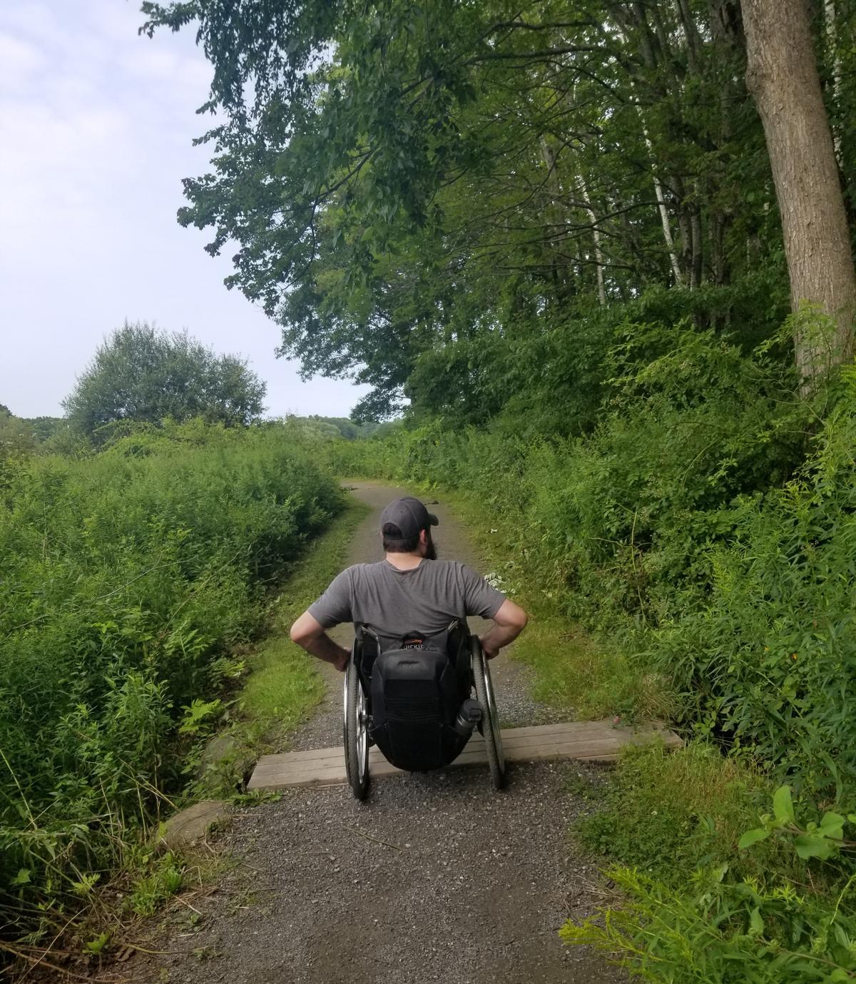 Enock crossing a short boardwalk on Eleanor's Trail. Photo credit: Enock Glidden