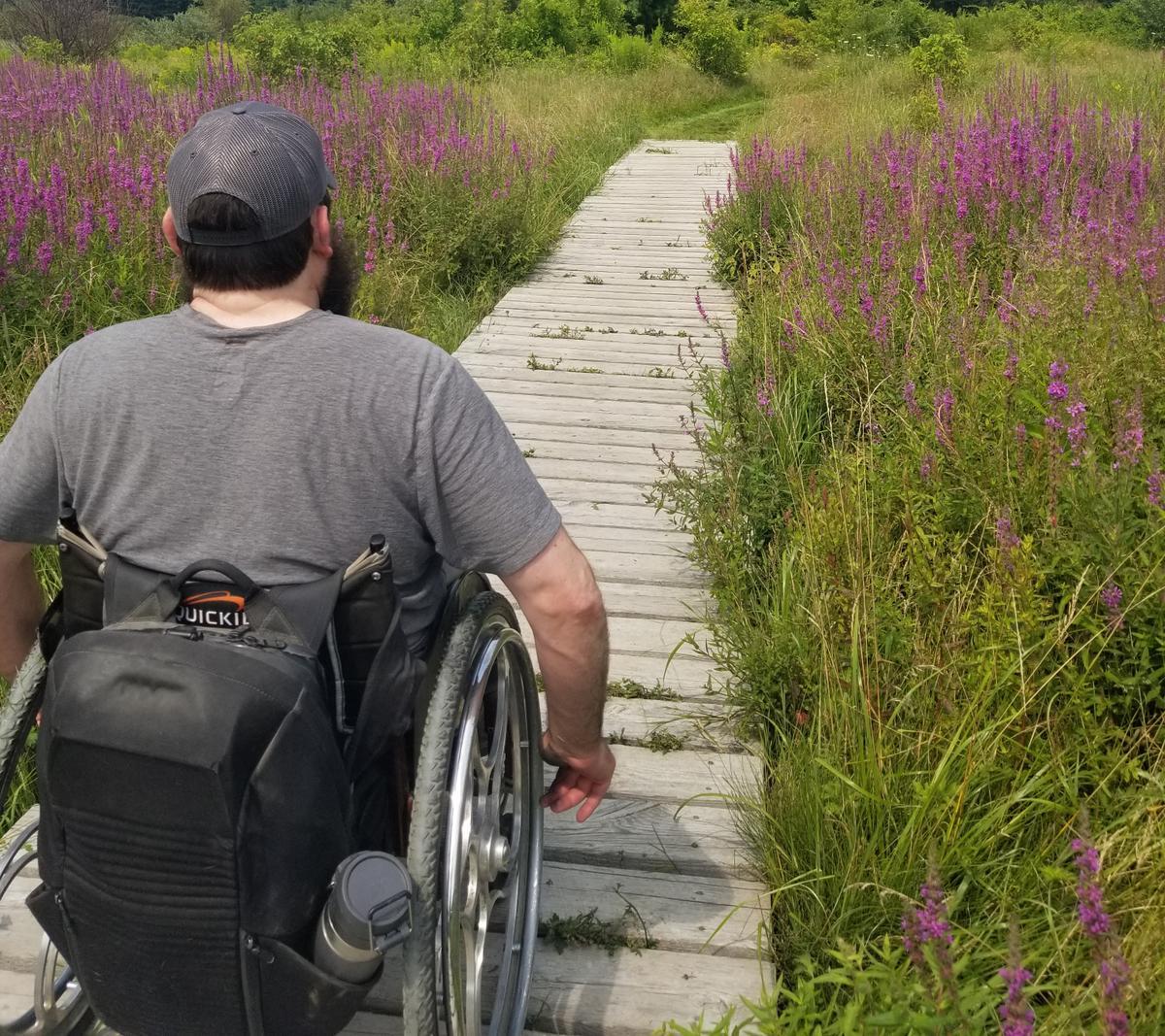 Enock crossing one of the boardwalks on Monty's Trail Loop. Photo credit: Enock Glidden
