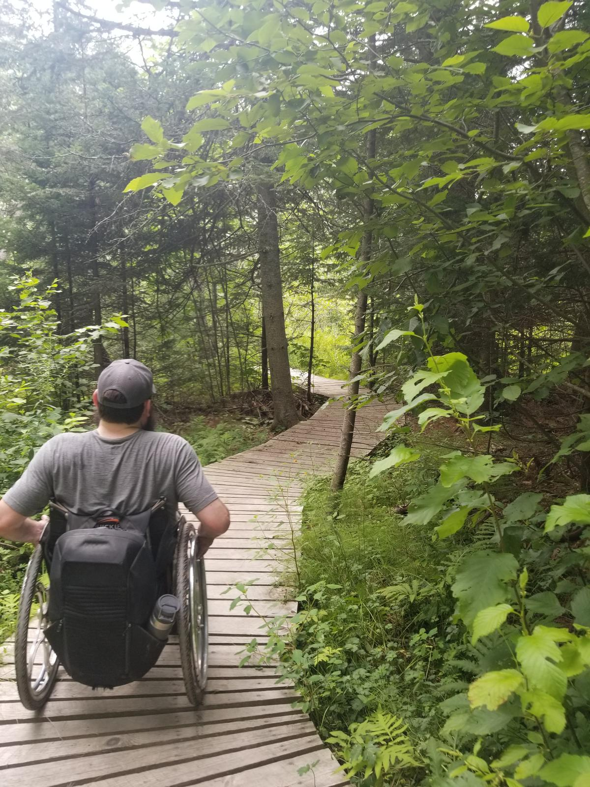 Enock crossing another boardwalk through the woods. Photo credit: Enock Glidden