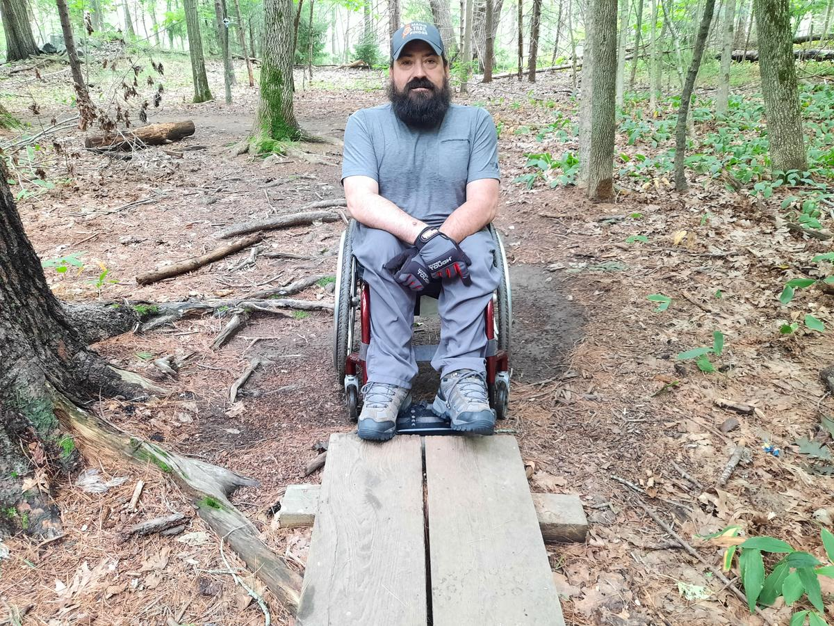 A man in a wheelchair sits next to a bog bridge that is two narrow for his chair.