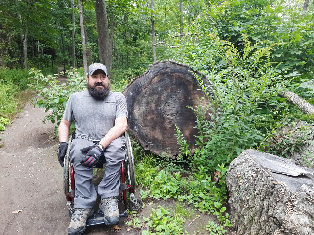 Enock next to a large downed tree. Photo credit: Enock Glidden