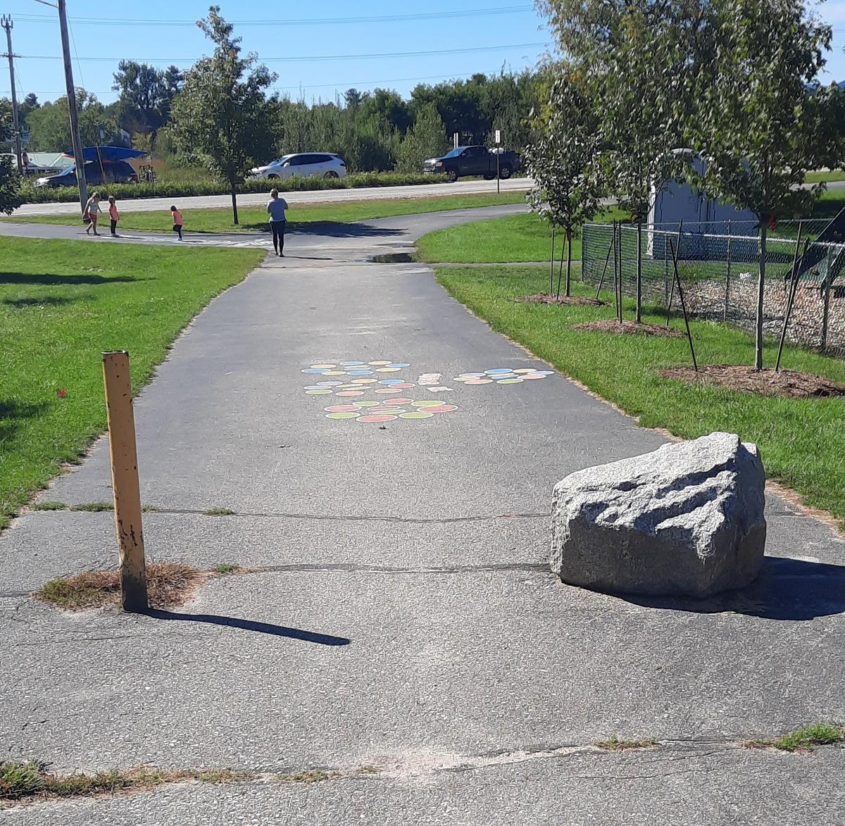 A rock and a pole block entrance to the Bethel Pathway to motorized vehicles, but allow wheelchairs and other wheeled devices through. Photo credit: Enock Glidden