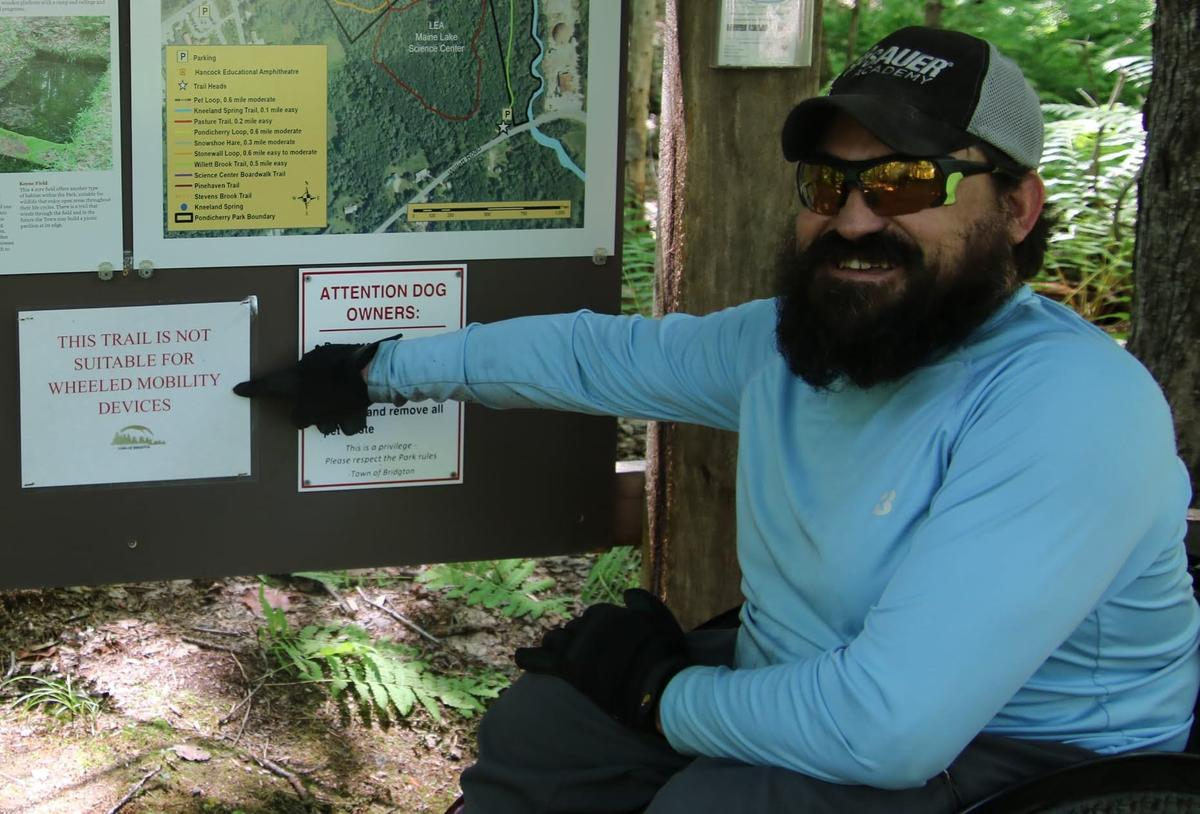 Enock pointing out the sign stating that the trail is not suitable for mobility devices.