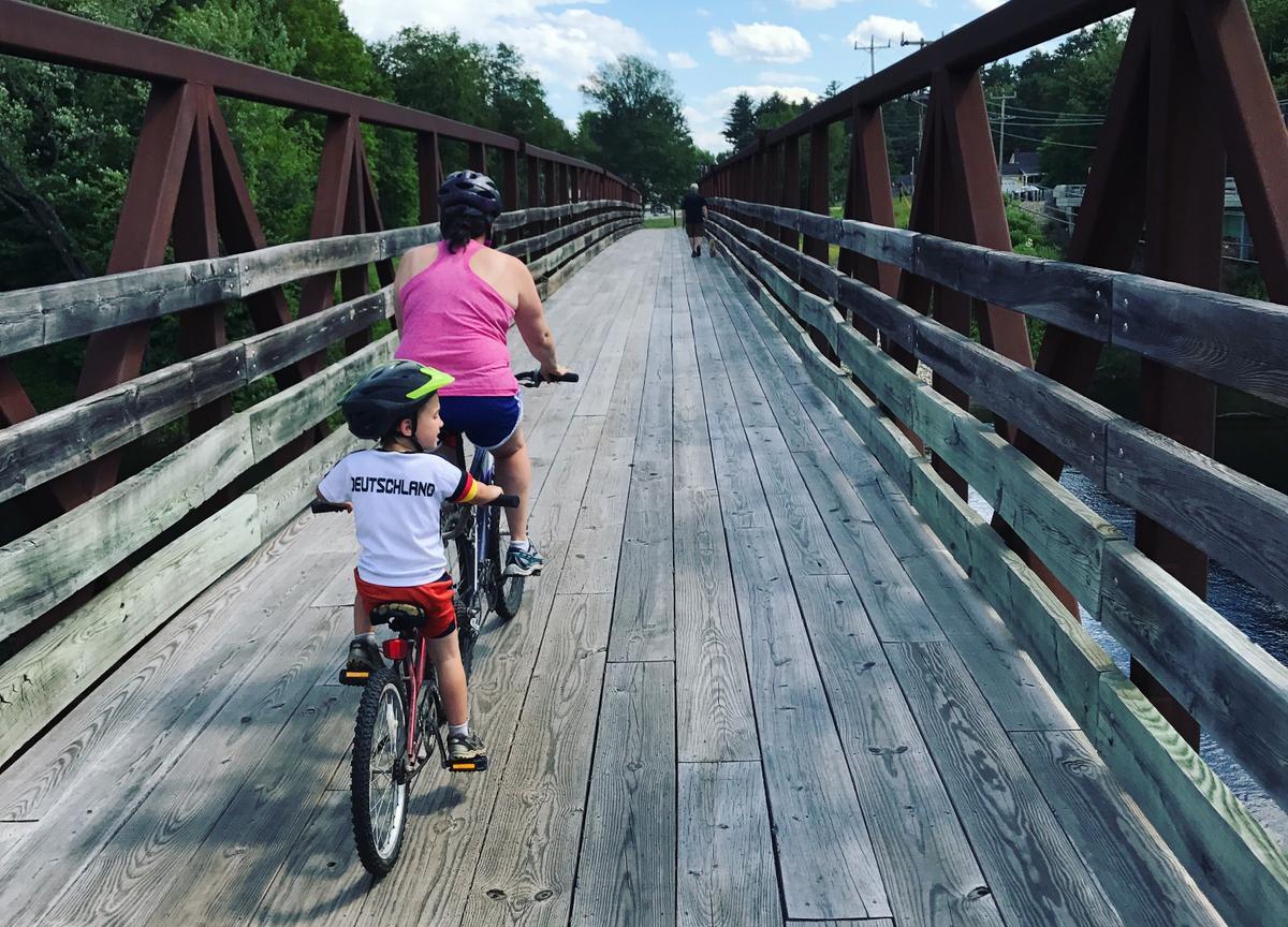 Biking over the bridge on the Bethel Pathway.