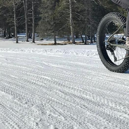 A fat biker bikes over snow following a trail of other bike tracks.