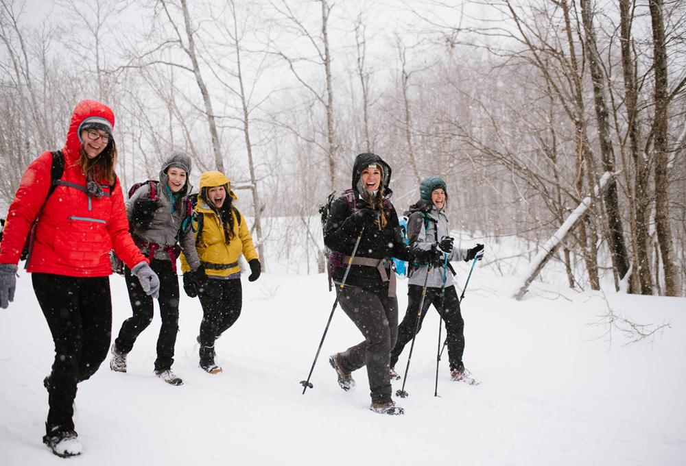 A group of women snowshoes in falling snow