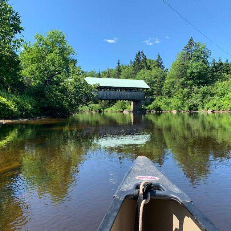 A calm river with a covered bridge in the background
