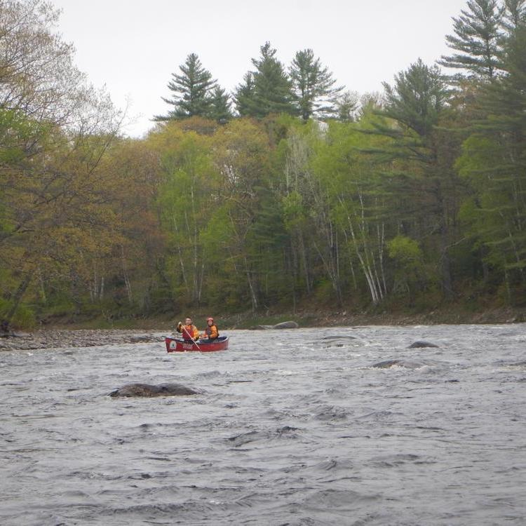 Two people paddle a canoe through a riffle on a wide river