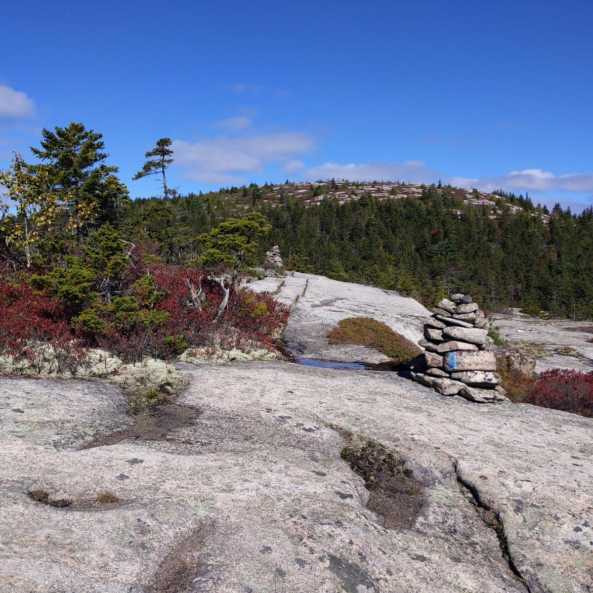 A rock cairn indicates the direction of the trail as it passes over a rock ledge