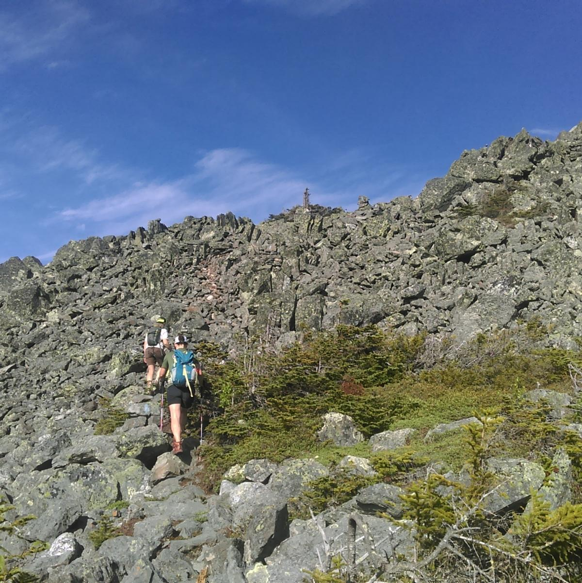 Many jumbled rocks make up the talus slope that two women are hiking over