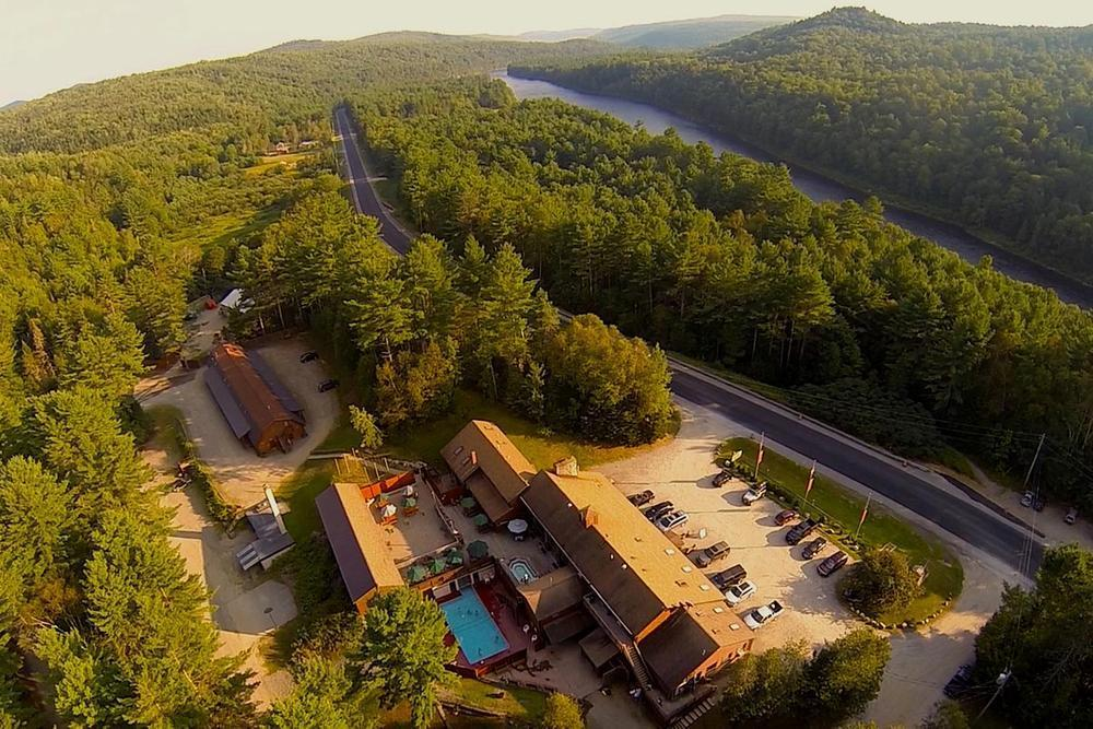An aerial view of the resort with the restaurant and pool in the foreground and the Kennebec River in the background