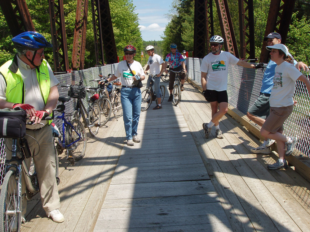 Cyclists Enjoy the view over the Machias River in Whitneyville (Credit: Sunrise Trail Coalition)