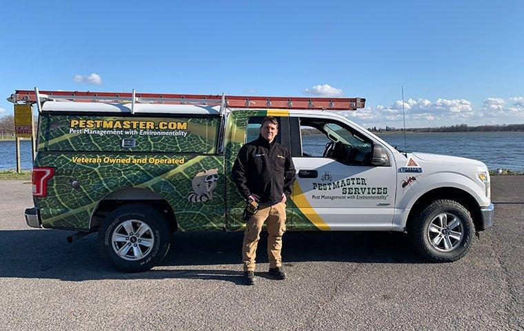 a pest management professional standing by a service vehicle