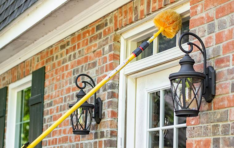 man sweeping exterior of house