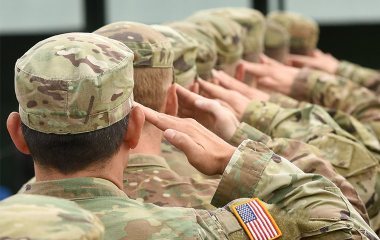 soldiers on a military base saluting flag