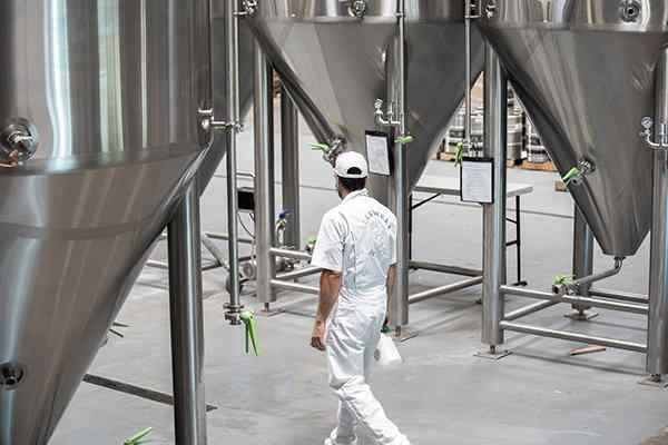 tech inspecting inside brewery