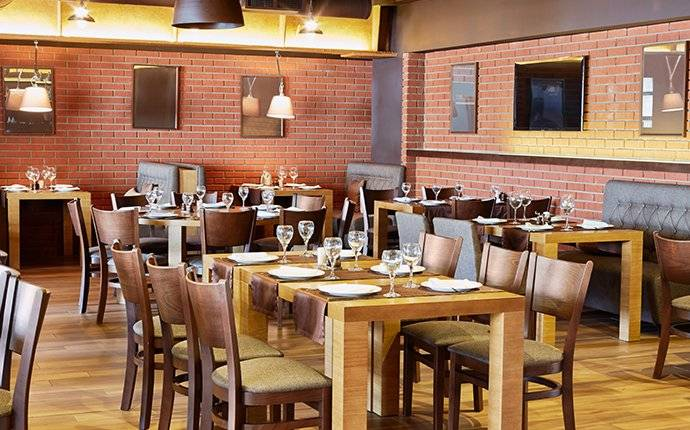 tables and chairs set up inside of a restaurant requiring commercial pest control