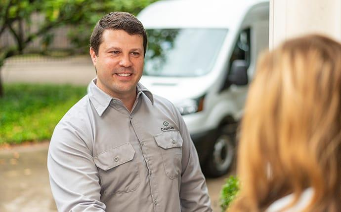 pest control technician greeting a homeowner in cadillac maine