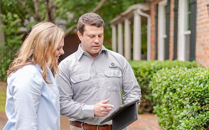 pest control technician talking with homeowner using software in cadillac maine