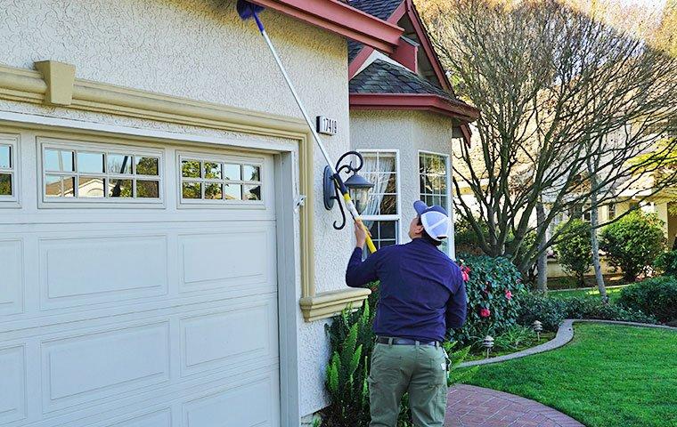 technician dewebbing residential home