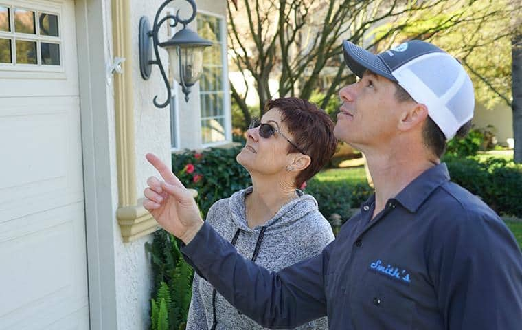 pest control technician looking at home with customer