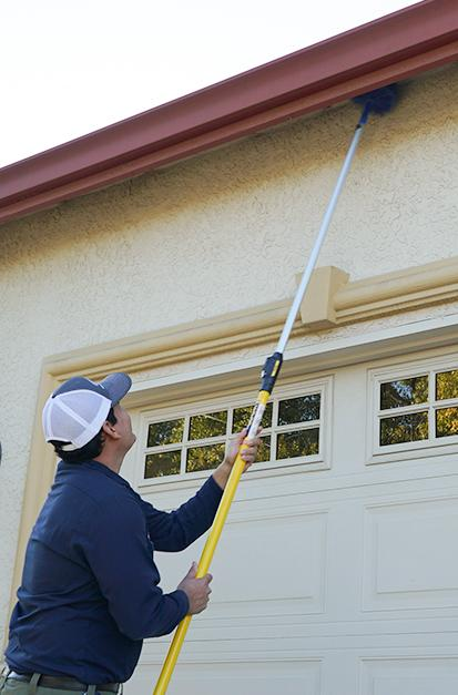 san francisco pest control tech removing cobwebs