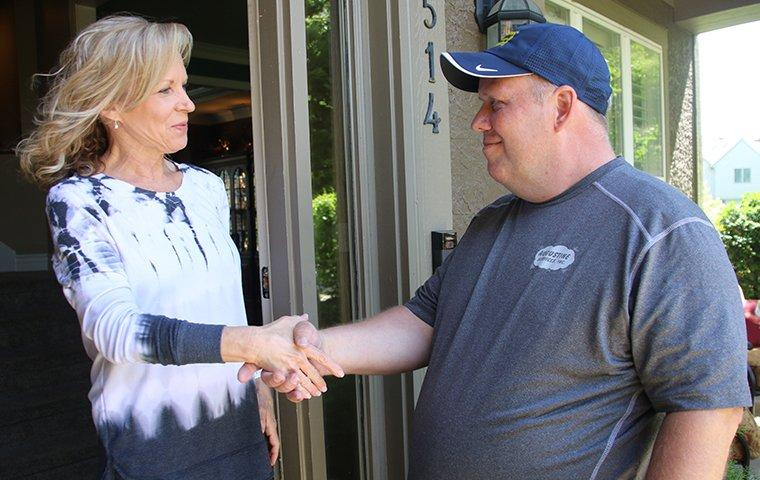 augustine exterminators technician shaking hands with a smiling customer in kansas city