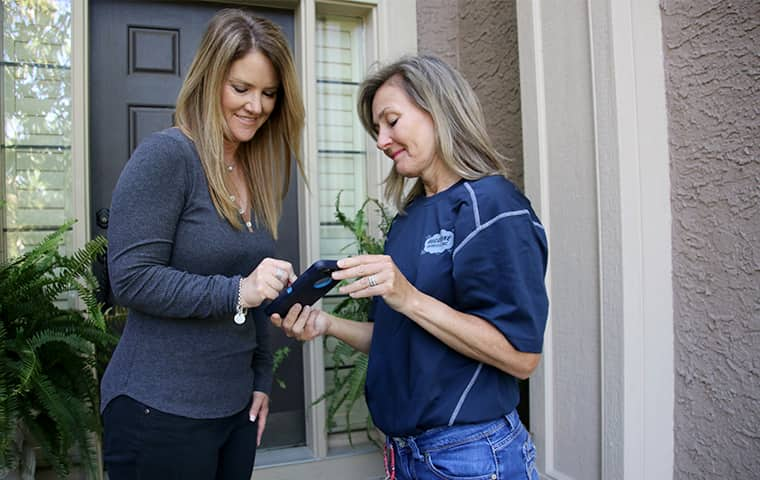 a pest control service technician meeting with a homeowner