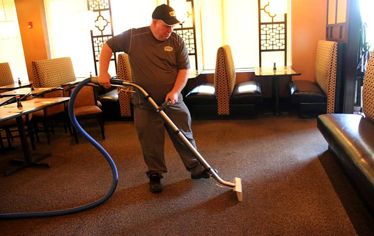 an augustine exterminators servie technician performing professional carpet cleaning inside of a kansas city commercial business