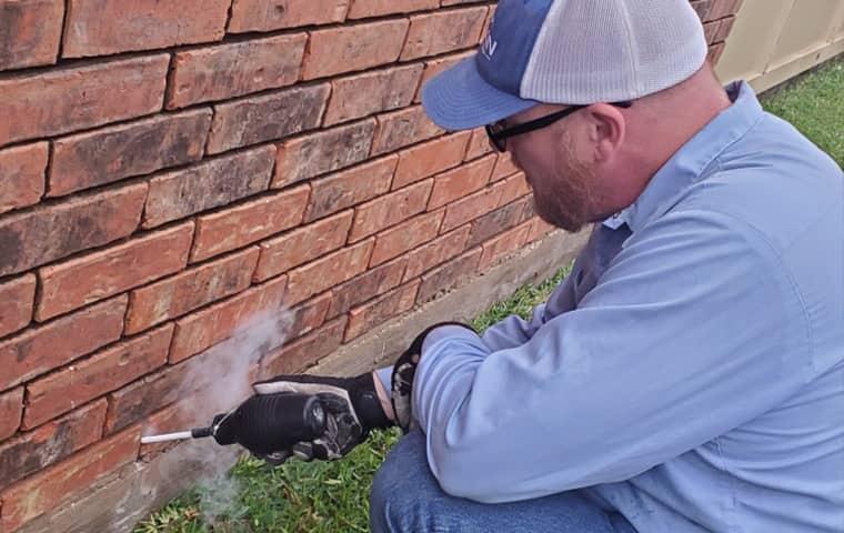 a falkin pest control service technician treating the exterior of a home in denver colorado
