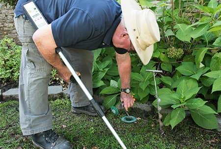 technician checking termite bait station