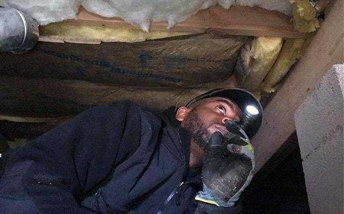 pest control technician inspecting home