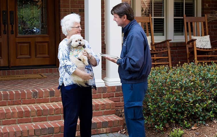 a pest control technician visiting with a raleigh north carolina homeowner