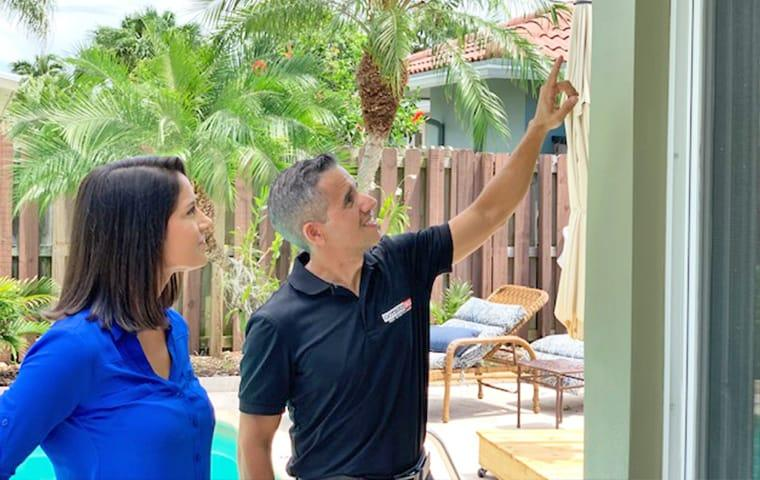 a homeowner and gotbugsikill owner outside of a residential home in boca raton florida