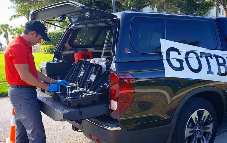 a gotbugsikill service technician preparing rodent stations on the back of the company vehicle in boca raton florida