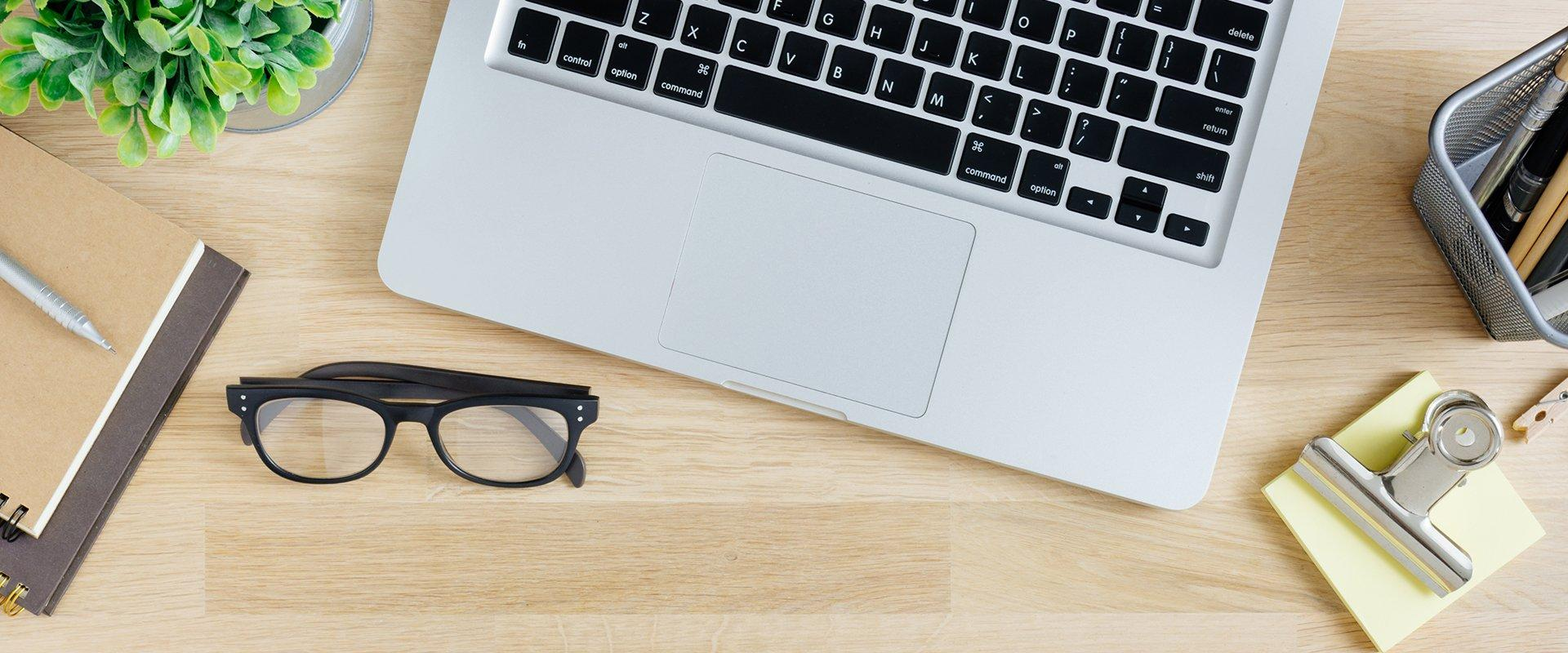 a laptop and glasses on a table