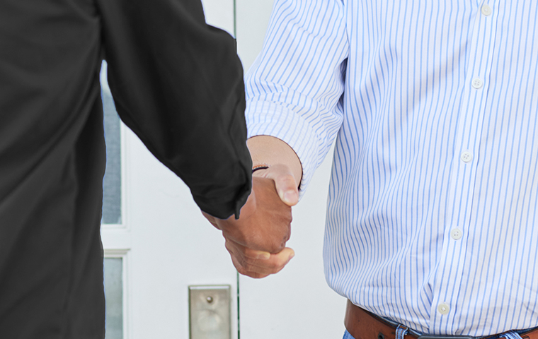 tech shaking hands with homeowner
