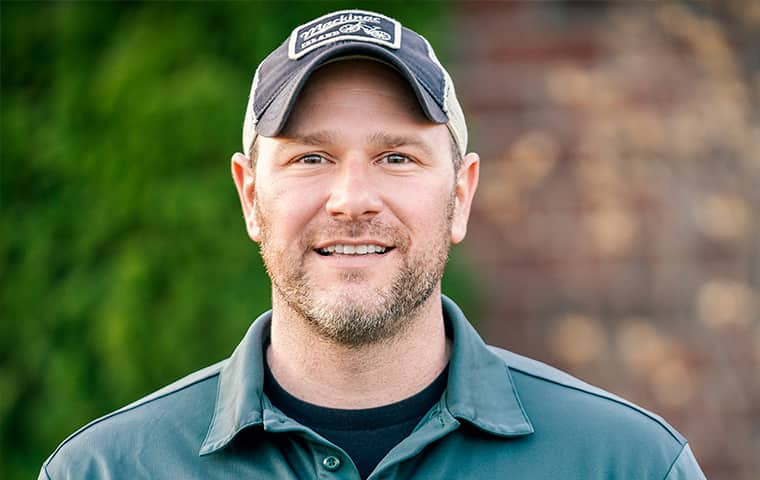 an eco pest control service technician outside of a home in port huron michigan